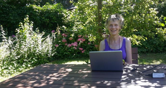 Berthe achter laptop in tuin